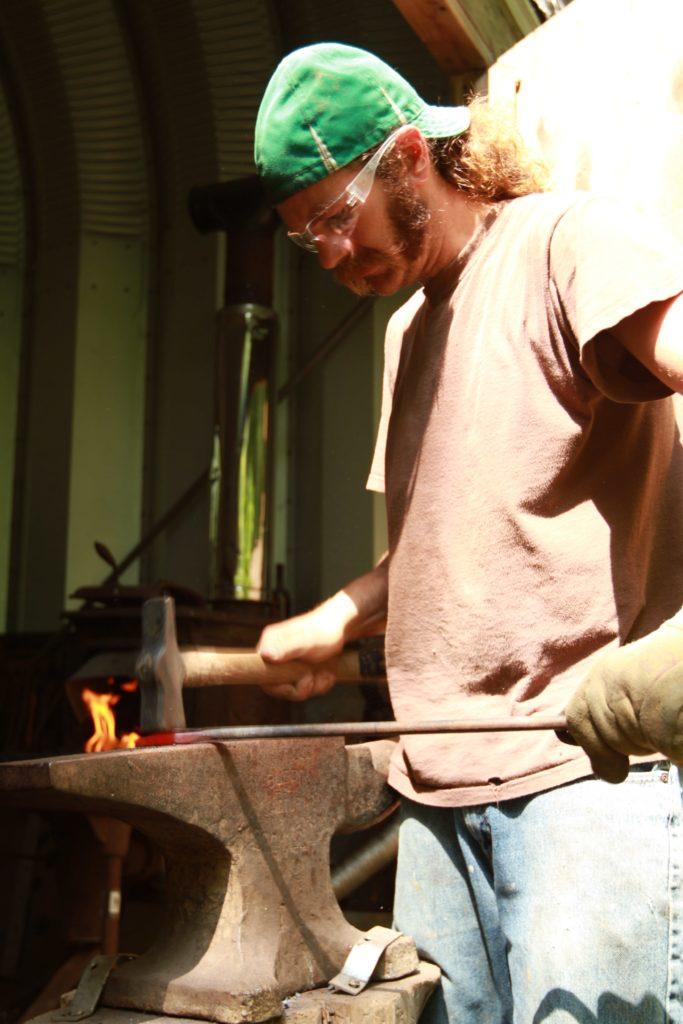Dustin Sustainabillies flattening metal on anvil